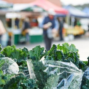 A macro shot of kale with market stalls in the background show the fresh produce to eat on The South West Edge south western australia road trip
